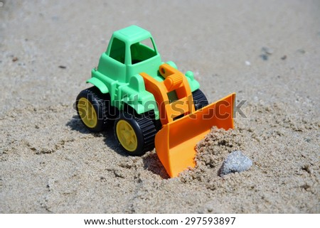 Bulldozer toy on the beach. Small dredge toy in the sand. - stock photo