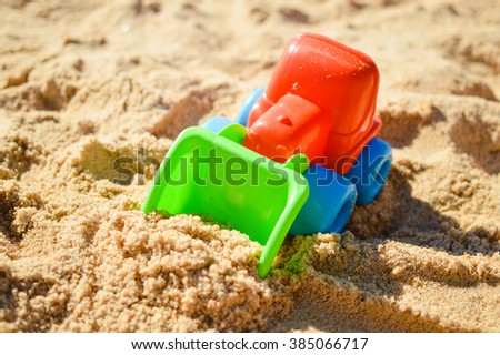 Bulldozer toy on the sandy sunny day outdoors background - stock photo