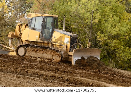 Bulldozer tractor works at moving soil and rock for a new commercial housing development. - stock photo