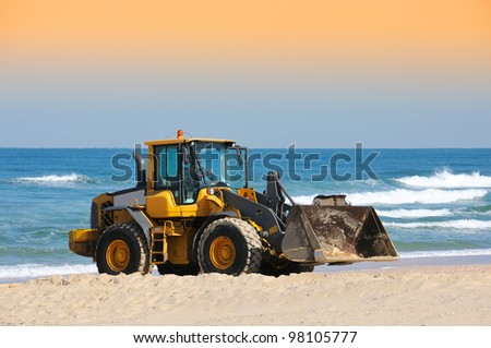 bulldozer working on a beach - stock photo