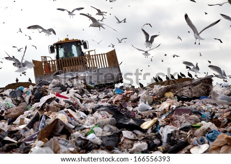 Bulldozer working on landfill with birds in the sky - stock photo