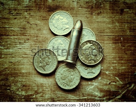 Bullet and pound coins - stock photo