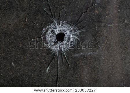 Bullet hole in glass on dirty grungy black background - stock photo