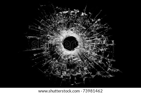 bullet hole in glass - real bullet hole closeup and isolated on black - stock photo