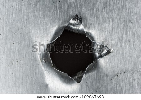 bullet hole in sheet metal - stock photo