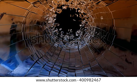 Bullet hole: pieces of shattered glass on black - stock photo