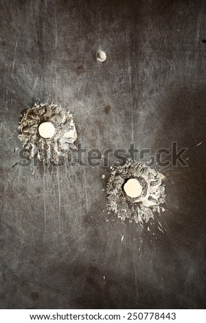Bullet holes in metal surface - stock photo