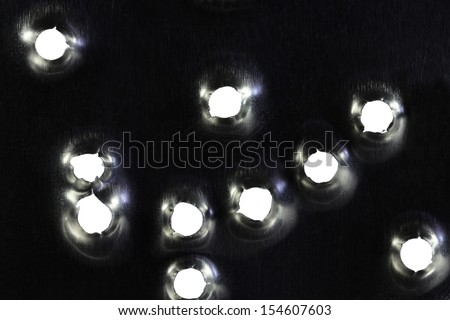 Bullet holes in the metal plate - stock photo