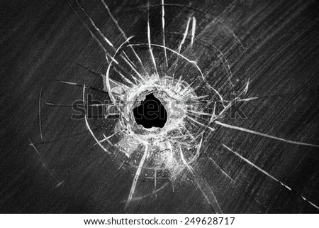 Bullet shot cracked hole on car windshield or accident damaged broken house window glass  - stock photo