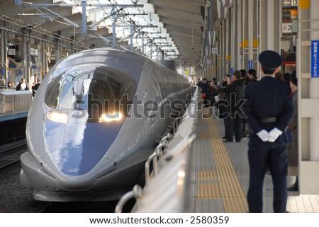 bullet train on platform at station - stock photo