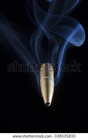 Bullet with a copper coating and smoke coming at the viewer - stock photo