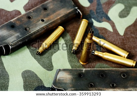 bullets and magazine on texture of soldier cloth background  - stock photo