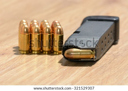 bullets and magazine on wood texture with natural pattern - stock photo