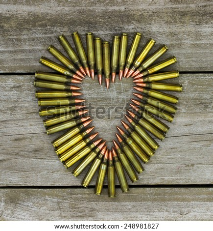 Bullets in the shape of heart on rustic wooden background - stock photo