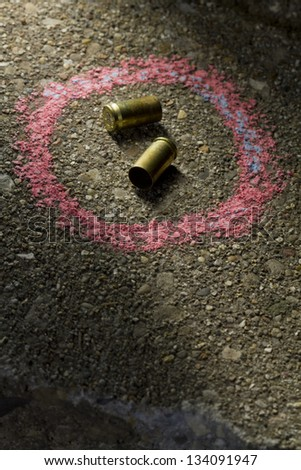 Bullets on ground with chalk drawn around - stock photo