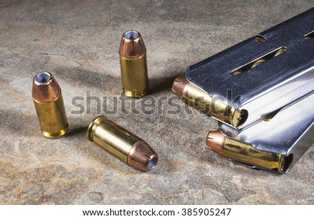 Bullets with hollow points for a handgun with magazines - stock photo