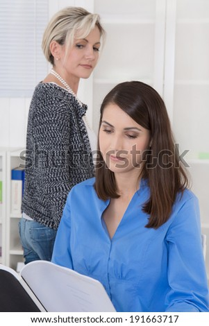 Bullying at work: older business woman is jealous. - stock photo