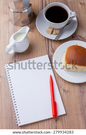 bun with coffee and notepad - stock photo