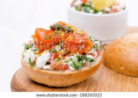 bun with cottage cheese, tomato and salmon on a wooden board, close-up - stock photo
