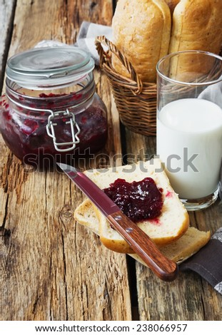 bun with seasoning in a basket, a glass of fresh milk and cherry jam on old wooden table. simple rustic food. - stock photo