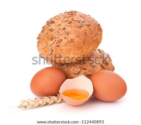 Bun with seeds and broken egg isolated on white background - stock photo