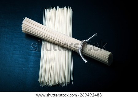 Bunch and pile of pasta spaghetti on a black background. Toned. - stock photo