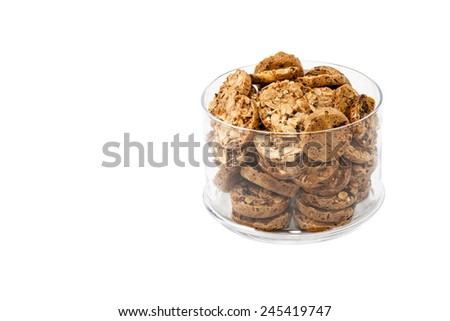 Bunch cookies with nuts and raisins in a round glass jar isolated on white background - stock photo