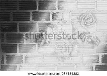bunch of artificial roses with filter colored and brick wall background in black and white tone - stock photo