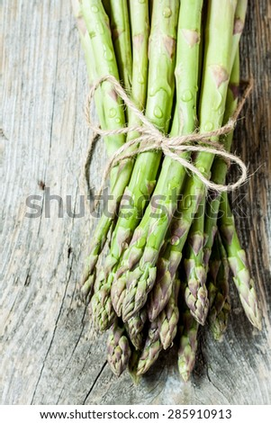 Bunch of asparagus on an old vintage wood background captured from above. Fresh harvest from the garden. - stock photo