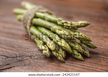 bunch of asparagus stems on brown wooden table. One of 5 greens a day - stock photo