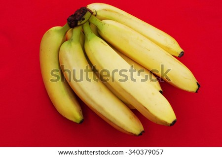 Bunch of bananas on red  background. Fresh organic Banana. Fresh bananas on  red kitchen table. Banan isolated on red.  Fresh fruits. Organic Banana. Sweet. Fruit. Food. - stock photo