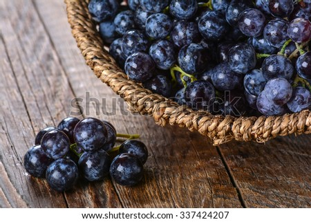 Bunch of black grapes in a wicker basket on a wooden table - stock photo