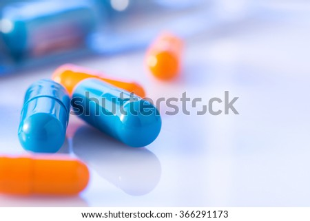 Bunch of blue and orange coloured pills.  - stock photo