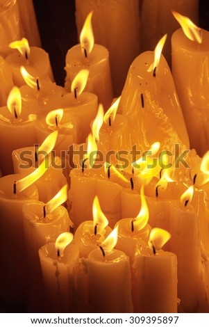 Bunch of candles burning at night - stock photo