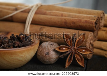 bunch of cinnamon sticks with nutmeg, anise and cloves, on rustic oak table - stock photo