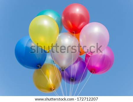 Bunch of colorful balloons in blue sky - stock photo