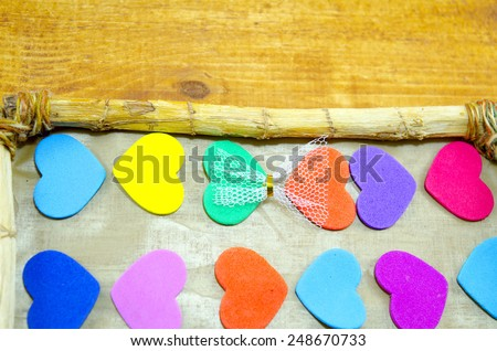 Bunch of colorful hearts in a wooden picture frame - stock photo