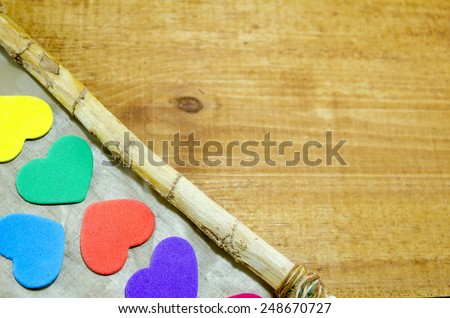 Bunch of colorful hearts on the edge of a crooked wooden picture frame - stock photo