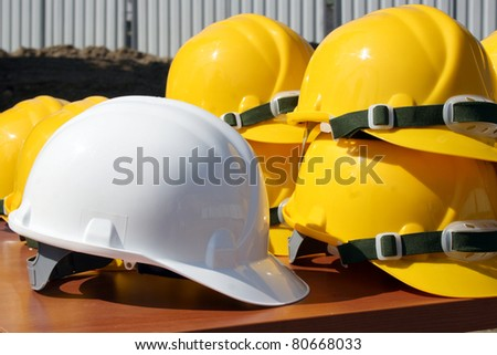 Bunch of construction helmets placed on wooden bench on construction site with one white wich is for head of staff - stock photo