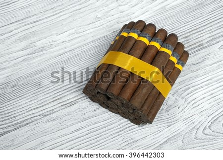 Bunch of Cuban cigars on wooden white  background tied with tape - stock photo