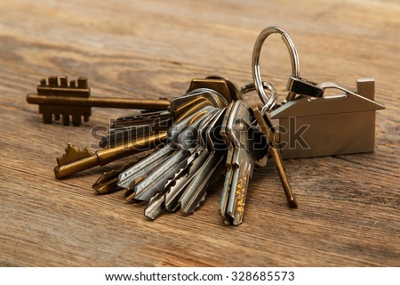 Bunch of different keys on wooden surface - stock photo