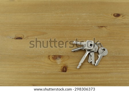 Bunch of different keys on wooden table. - stock photo