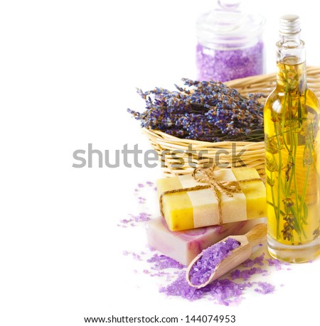 Bunch of dried lavender flowers, essential oil, soap and lavender sea salt on a white. - stock photo