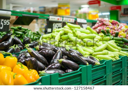 Bunch of eggplants and zucchini on boxes in supermarket - stock photo