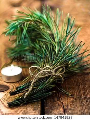Bunch of fir tree or pine branches and glowing candle on wooden dark old background. Closeup. - stock photo