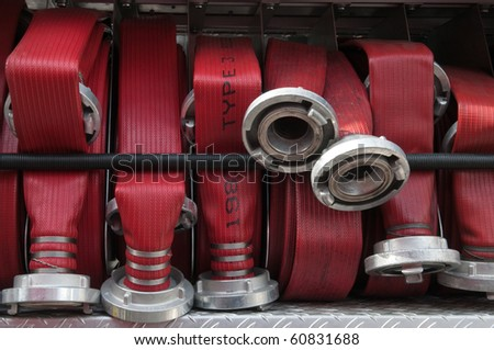 bunch of fire hoses on a firetruck - stock photo