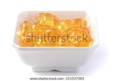 Bunch of fish oil capsules pills in bowl  - stock photo