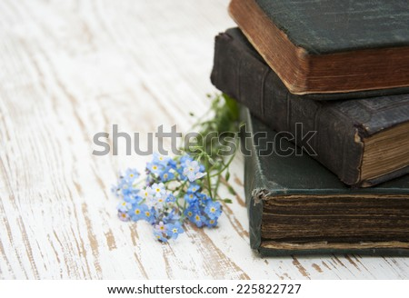 Bunch of forget-me-nots flowers and very old books - stock photo