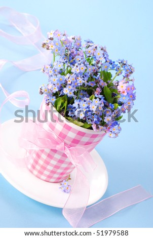 bunch of forget-me-nots in vase with ribbon  on blue background - stock photo
