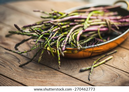 Bunch of fresh asparagus in copper dish on wooden table. Selected focus and shallow DOF - stock photo